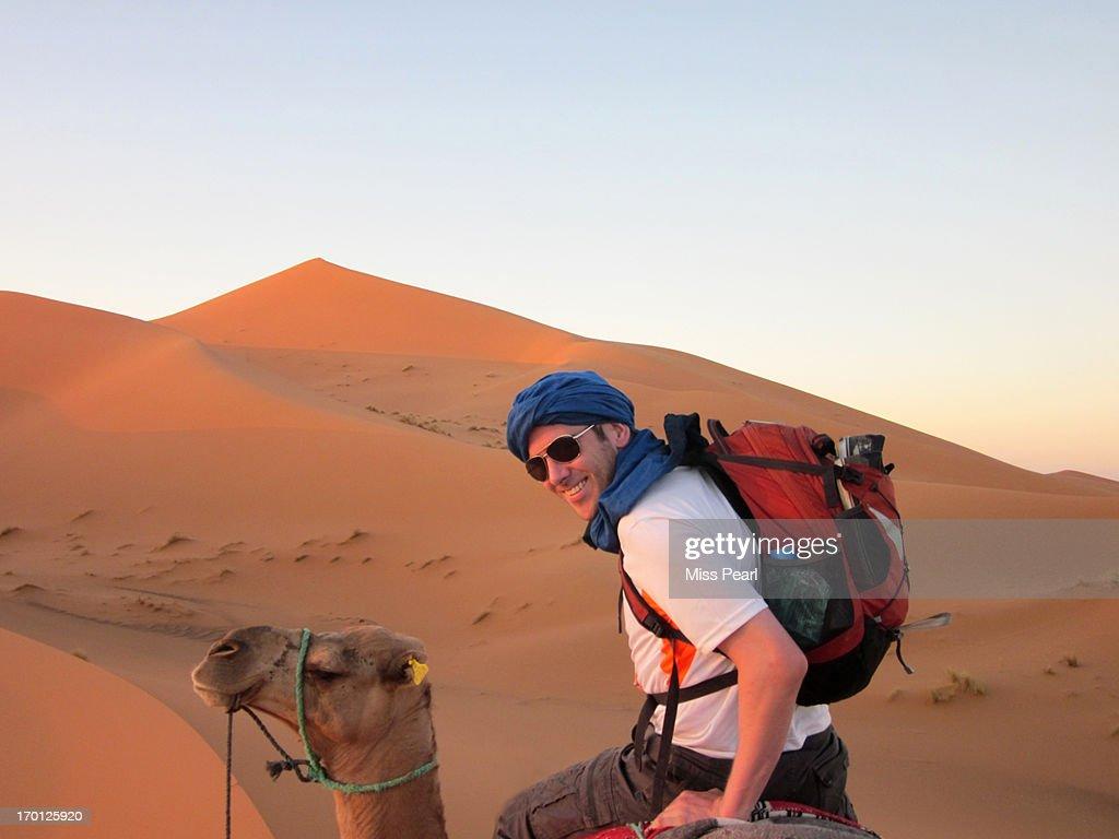 Young man enjoys Sahara camel safari