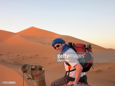 Young man enjoys Sahara camel safari