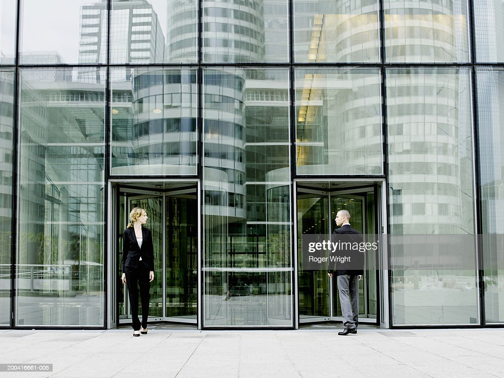 Young man entering building as young woman exits : Stock Photo