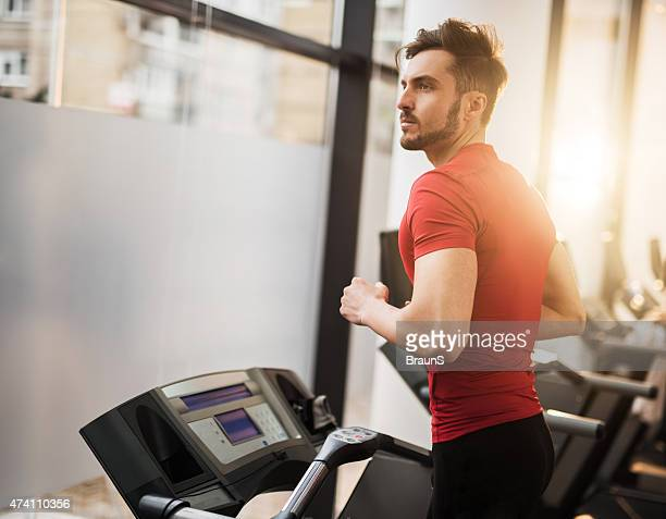 Young man exercising on a treadmill in a health club.