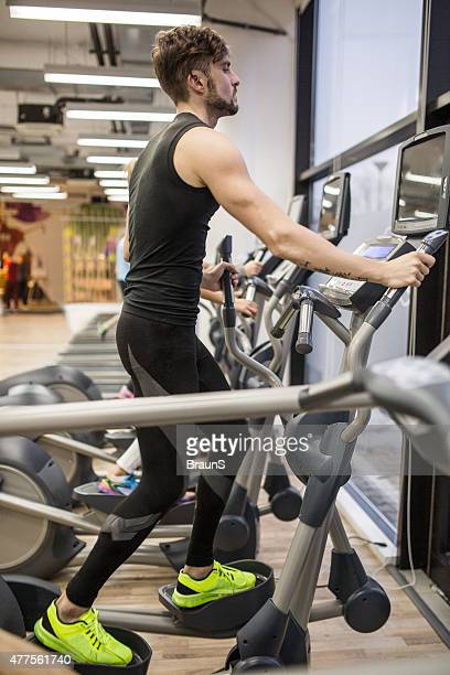 Young man exercising on cross trainer in a health club.