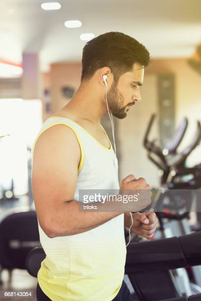 Young man exercising on cross trainer