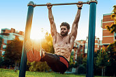 Fitness man doing stomach workouts on horizontal bar outdoors