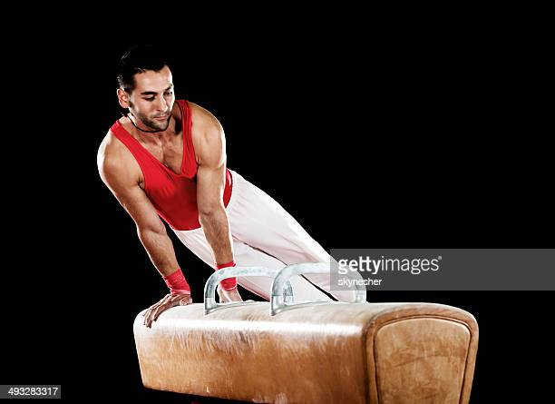 Young man exercising on pommel horse.