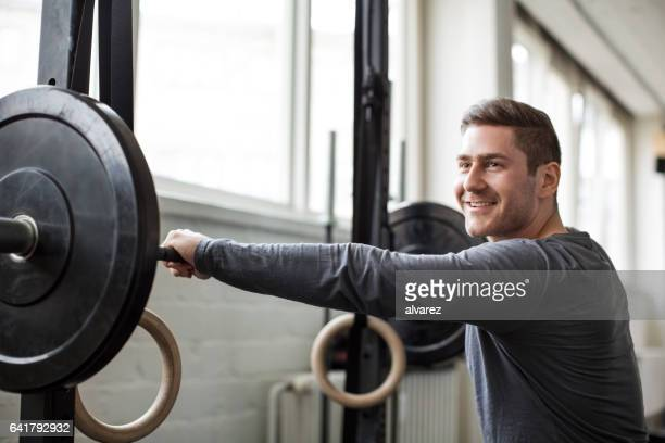 Young man exercising with barbell at gym