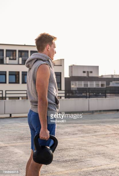 Young man exercising with kettle bell on a rooftop
