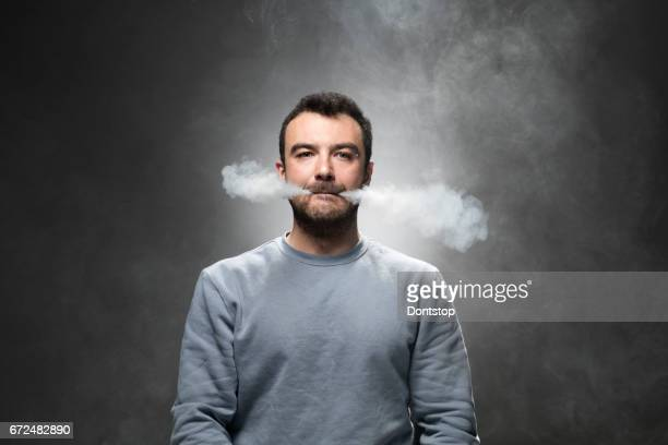 Young man exhales cloud of tobacco vapor from corners of mouth
