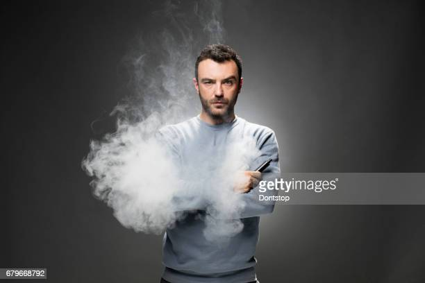 Young man exhales cloud of tobacco vapor from his noise.
