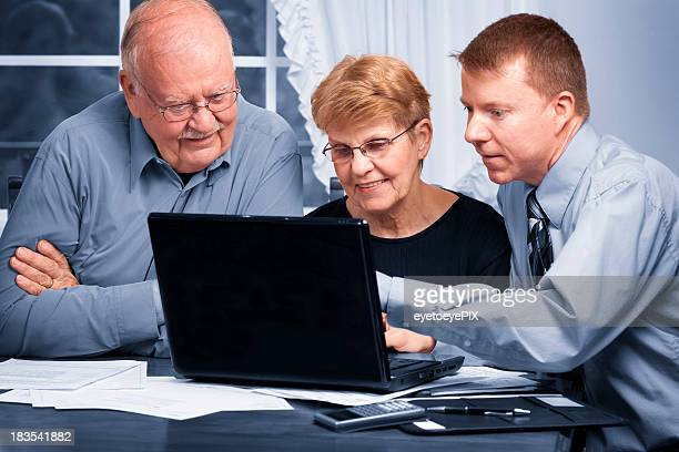 Young man explaining something on a laptop to senior couple