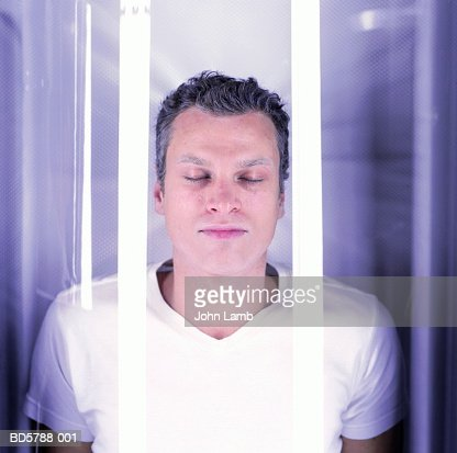 Young man, eyes closed, in cryogenics chamber, close-up