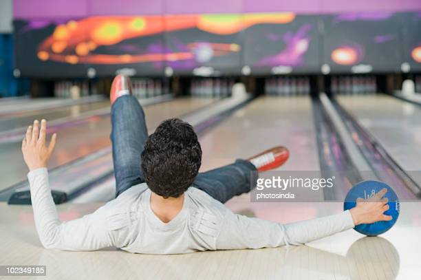 Young man falling in a bowling alley