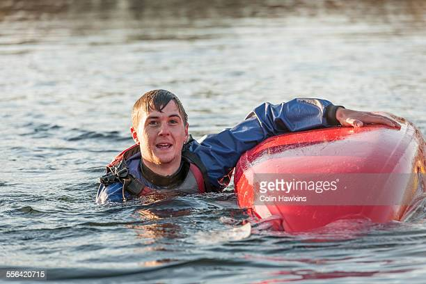 Young man falling in water with kayak