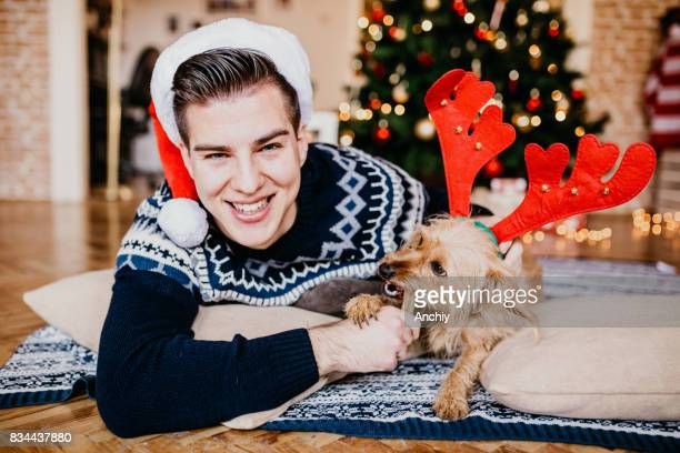 Young man feeding his cute dog in front of Christmas tree.