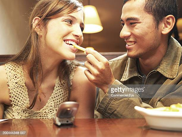 Young man feeding woman french fry in restaurant