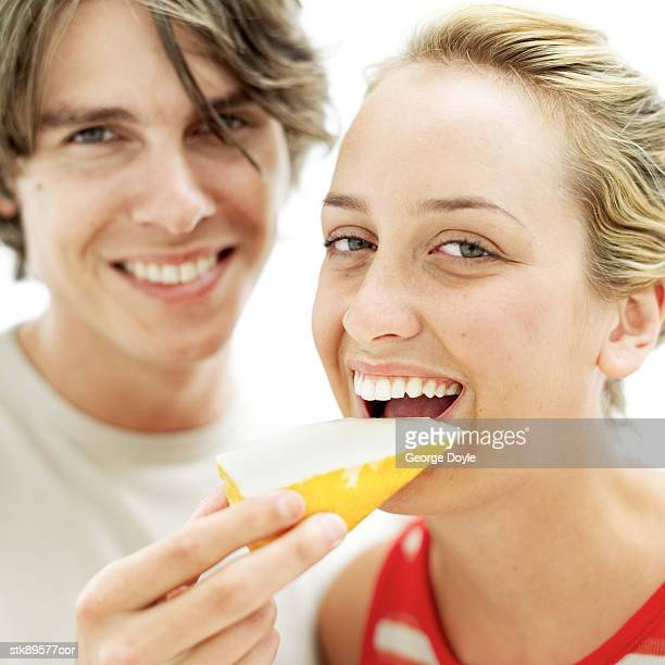 young man feeding young woman a slice of cheese