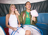 Young man feeding young woman popcorn on amusement park ride