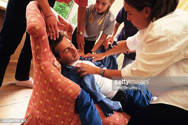 Young man feinted in armchair, four people attending