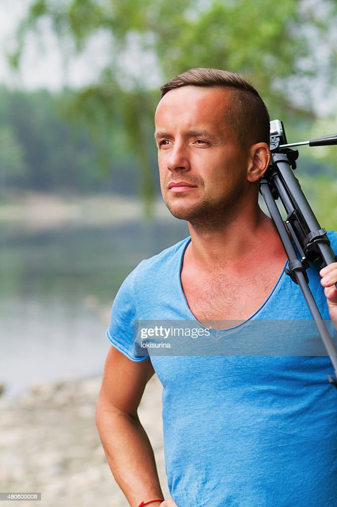 young man filmed on camera in nature : Stock Photo