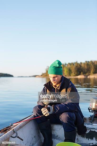 Young man fishing on boat
