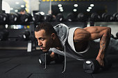 Young african-american man workout in fitness club. Black guy making plank or push ups exercise on dumbbells, training indoors, copy space