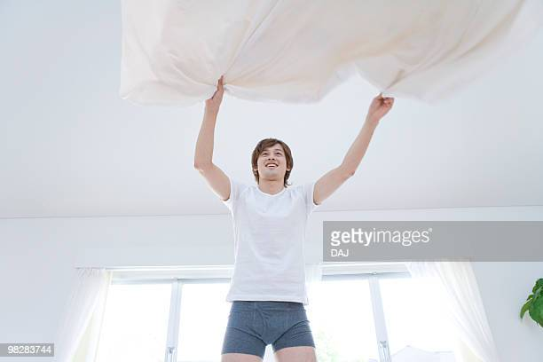 Young man fixing bed