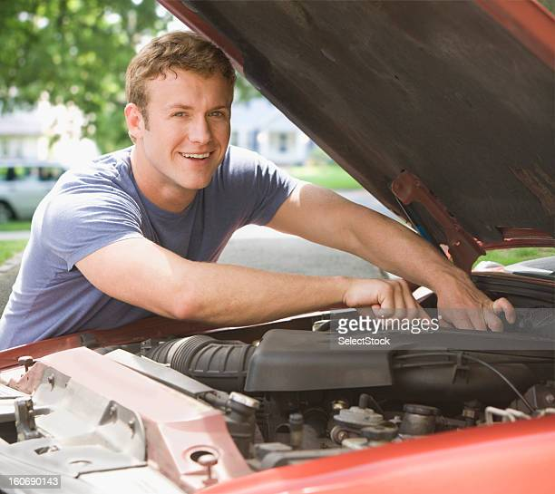 young man fixing engine of his car smiling