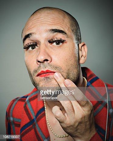 Young man fixing lipstick