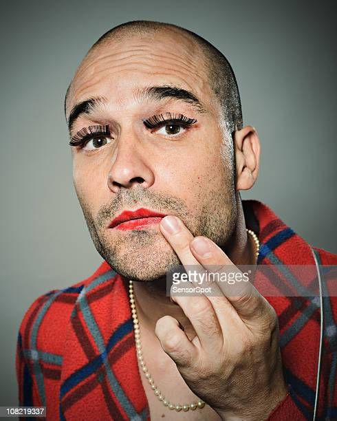 Young man fixing lipstick
