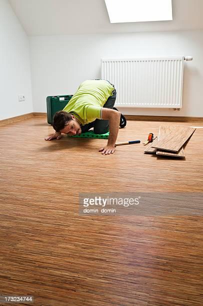 Giovane uomo risoluzione pavimento in legno