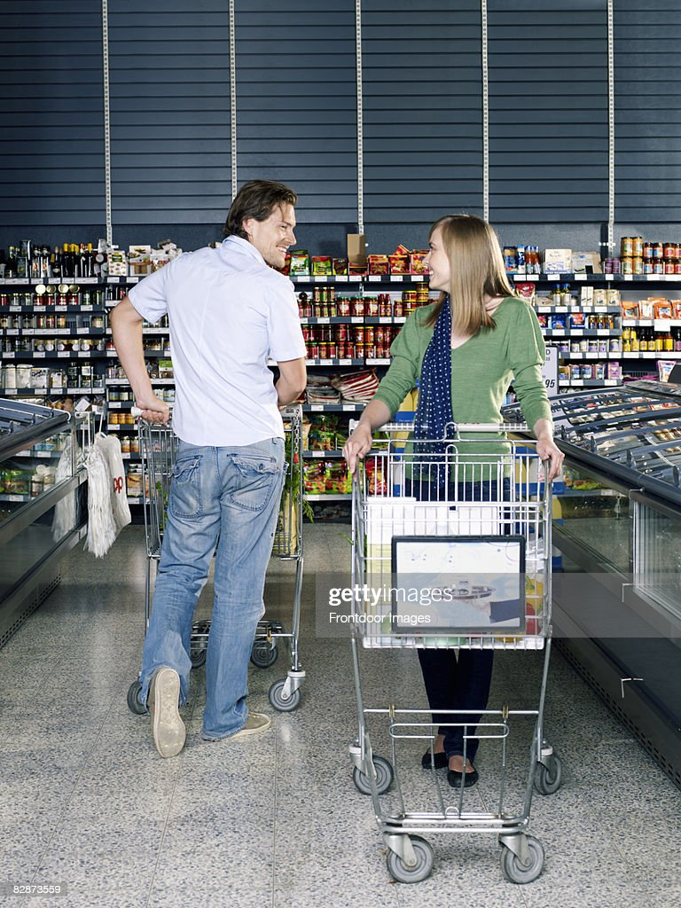 young man flirting with young woman in supermarket : Stock Photo