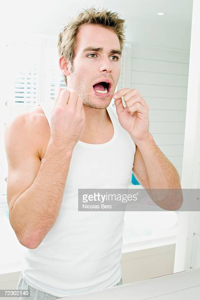 Young man flossing teeth in front of bathroom mirror