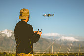 A young man outside on a clear day flying a drone with the Wasatch Mountains in the backgroundu