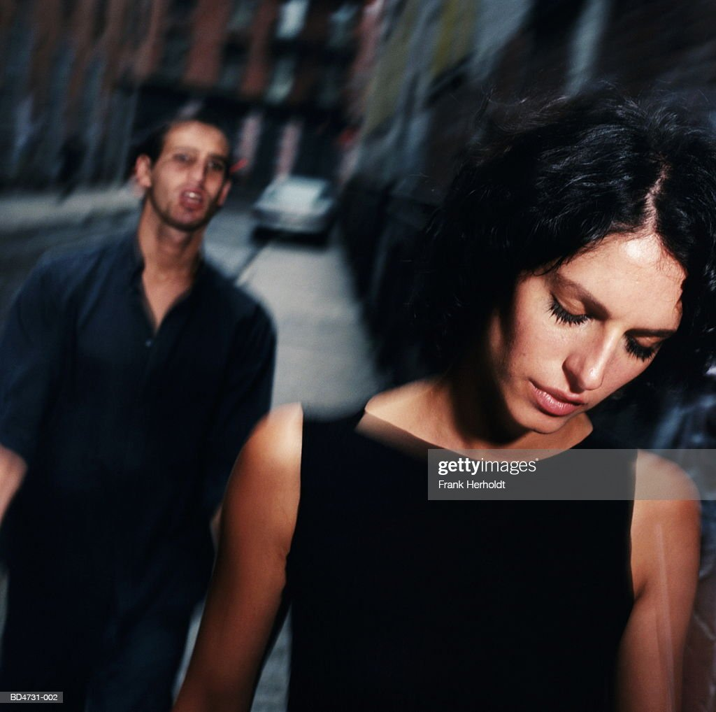 Young man following woman along street (blurred motion) : Stock Photo