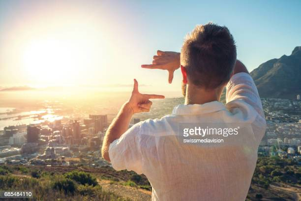 Young man framing sunrise with hands