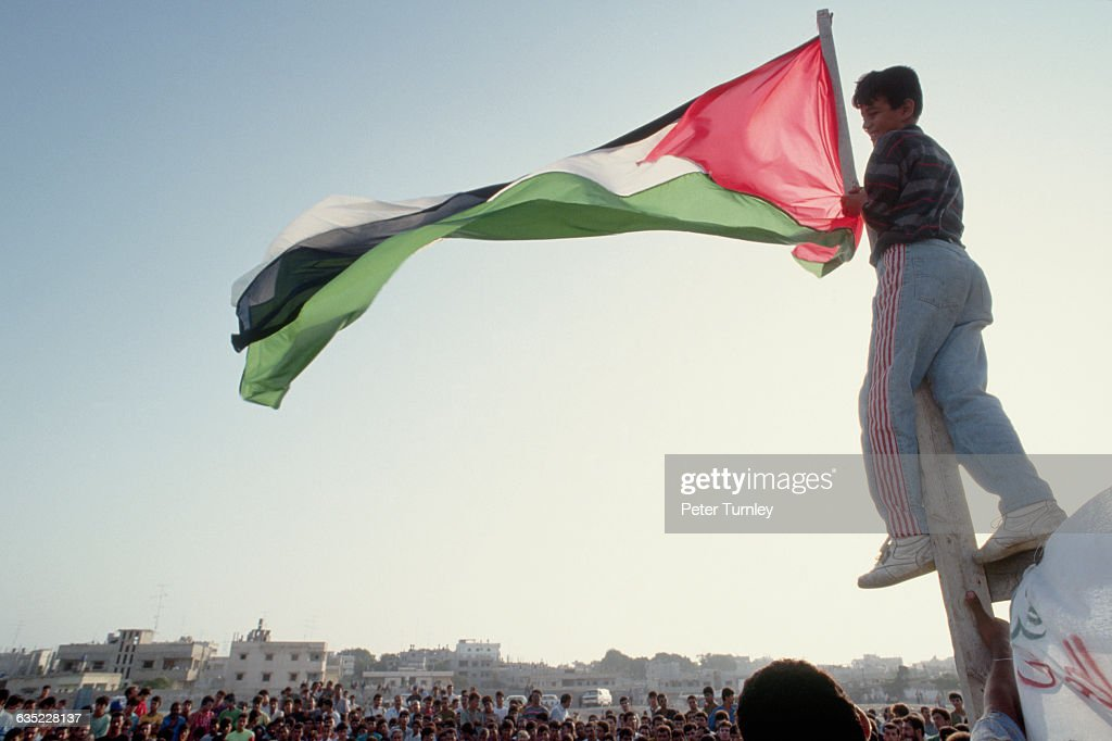 A young man freely flies the previously banded Palestinian flag while on the streets of Gaza below tens of thousands of Palestinians celebrate the...