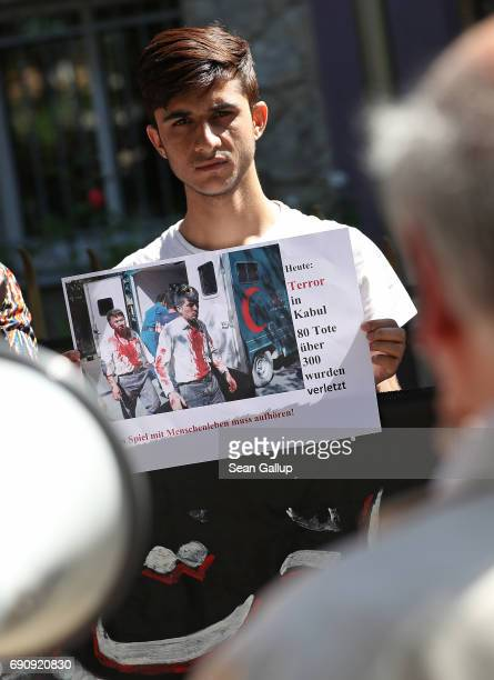 A young man from Afghanistan protesting against deportations holds up a photo of today's bombing in Kabul outside the Afghan Embassy on May 31 2017...