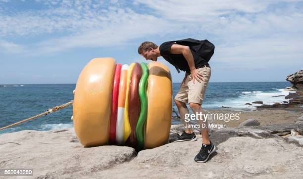 A young man from the Netherlands mocks taking a bite out of 'What a Tasty Looking Burger' by James Dive at Sculpture By The Sea on October 18 2017 in...