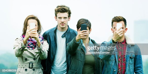 Young man frowns as friends are obsessed with phones