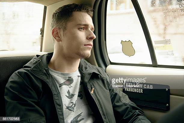 Young man gazing out from yellow cab window