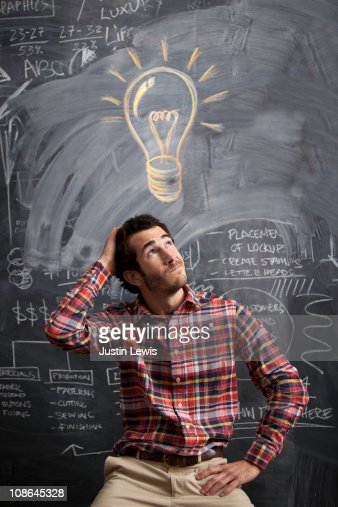 young man getting an idea with light bulb above : Foto de stock