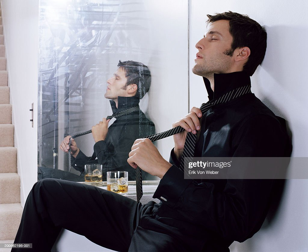 Young man getting dressed, reflection in mirror, side view : Stock Photo