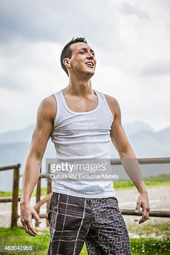 Young man getting soaked in rain, Tyrol, Austria