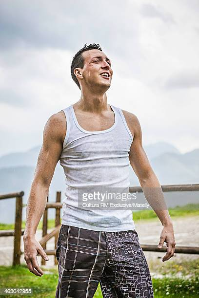 Young man getting soaked in rain, Tyrol, Austria