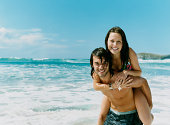 Young Man Gives a Woman a Piggyback on the Beach, by the Water's Edge
