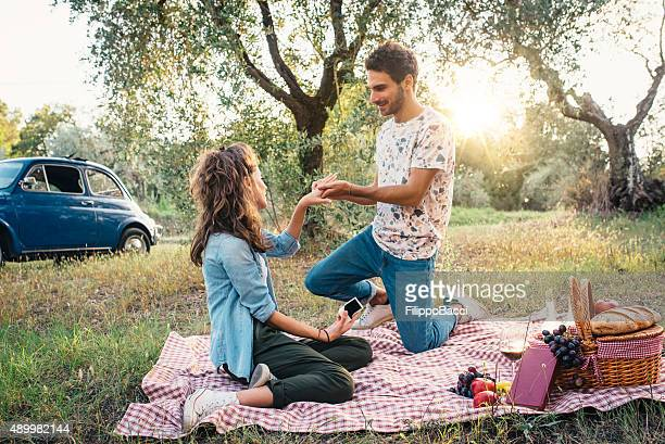 Young Man Giving Engagement Ring To A Beautiful Young Woman