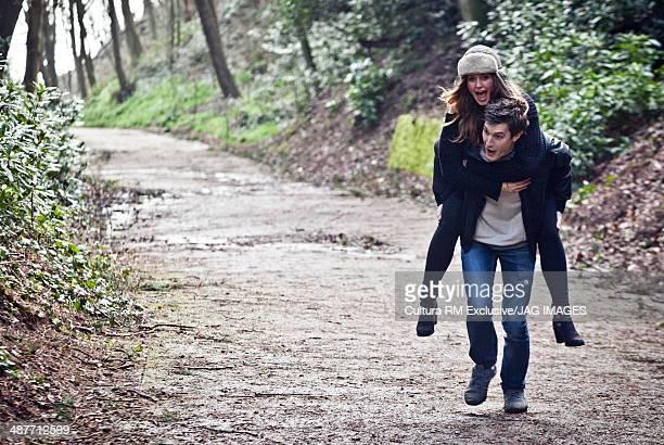 Young man giving girlfriend a piggy back through forest
