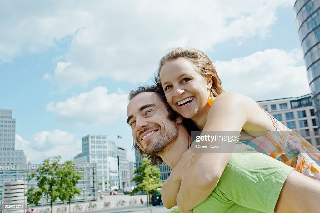 Young man giving piggy back ride to woman in city : Stock Photo