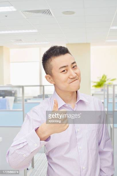 Young man giving thumbs up sign in office, portrait