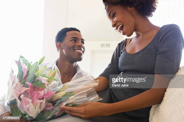 Young man giving woman bouquet