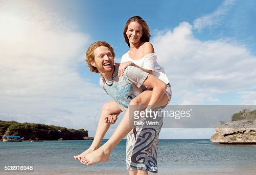 Young man giving woman piggyback ride on beach : ストックフォト